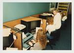A female professor helps two female students using typewriters