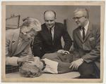 From the left: Mrs. Betty Luisant, Dr. Peter Bosomworth, and Dr. Charles Mobler demonstrate a medical technique on a mannequin
