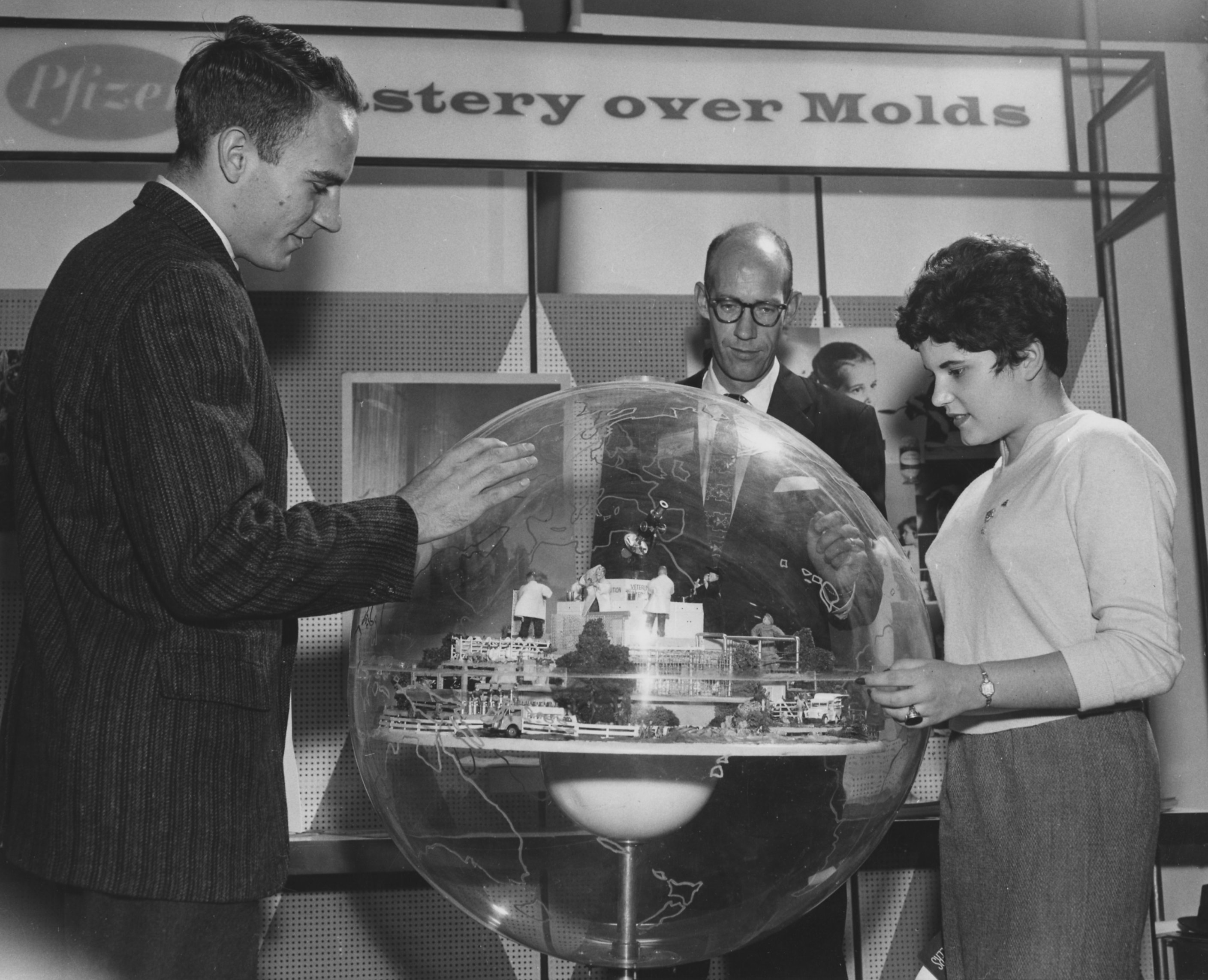 Two men and a woman looking at a model near the Pfizer display at